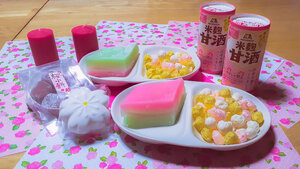 Hishi mochi, amazake, and hina arare displayed on a table at home for Girls' Day in Japan